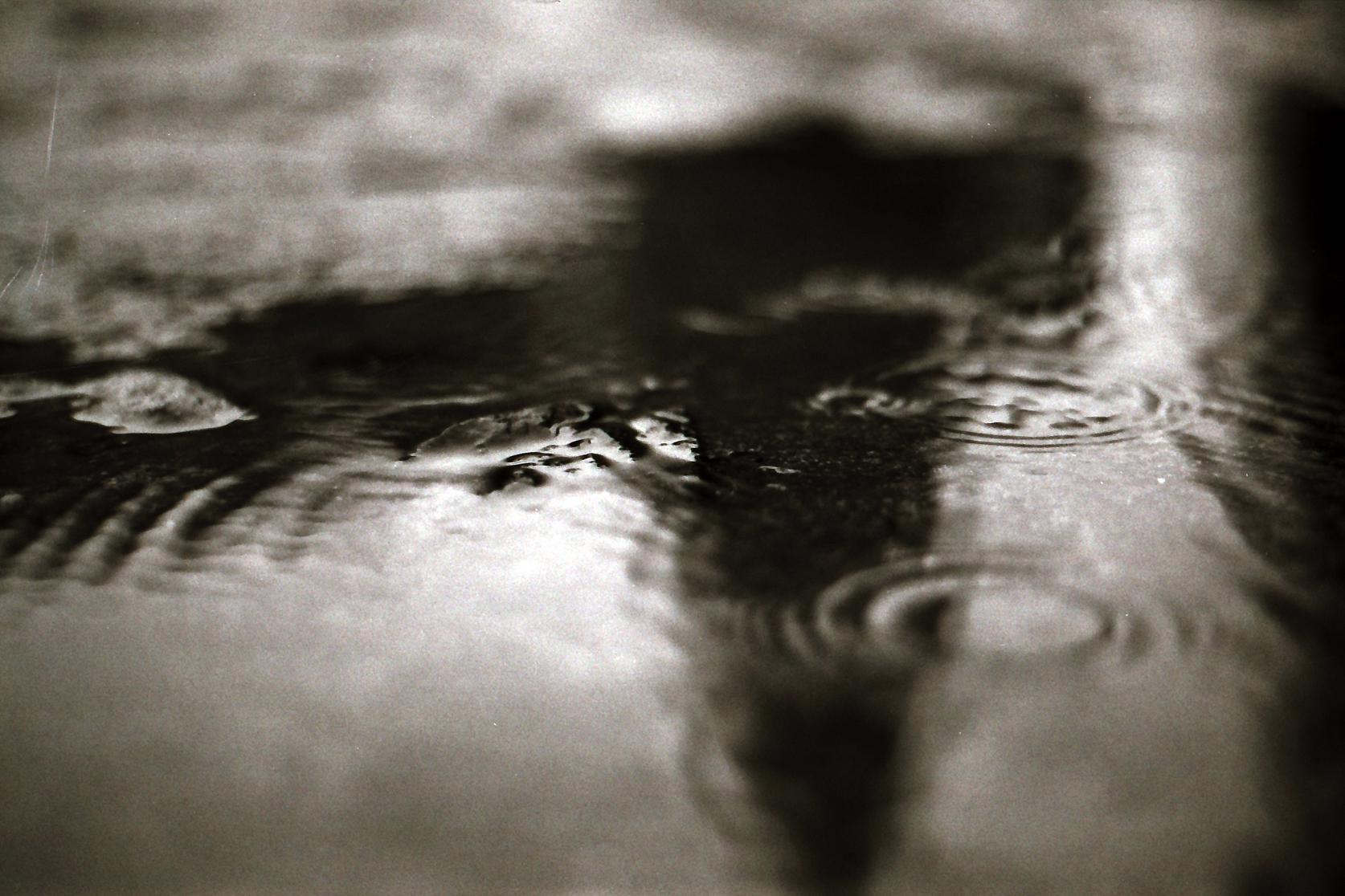Regentropfen aus Pfützenoberfläche