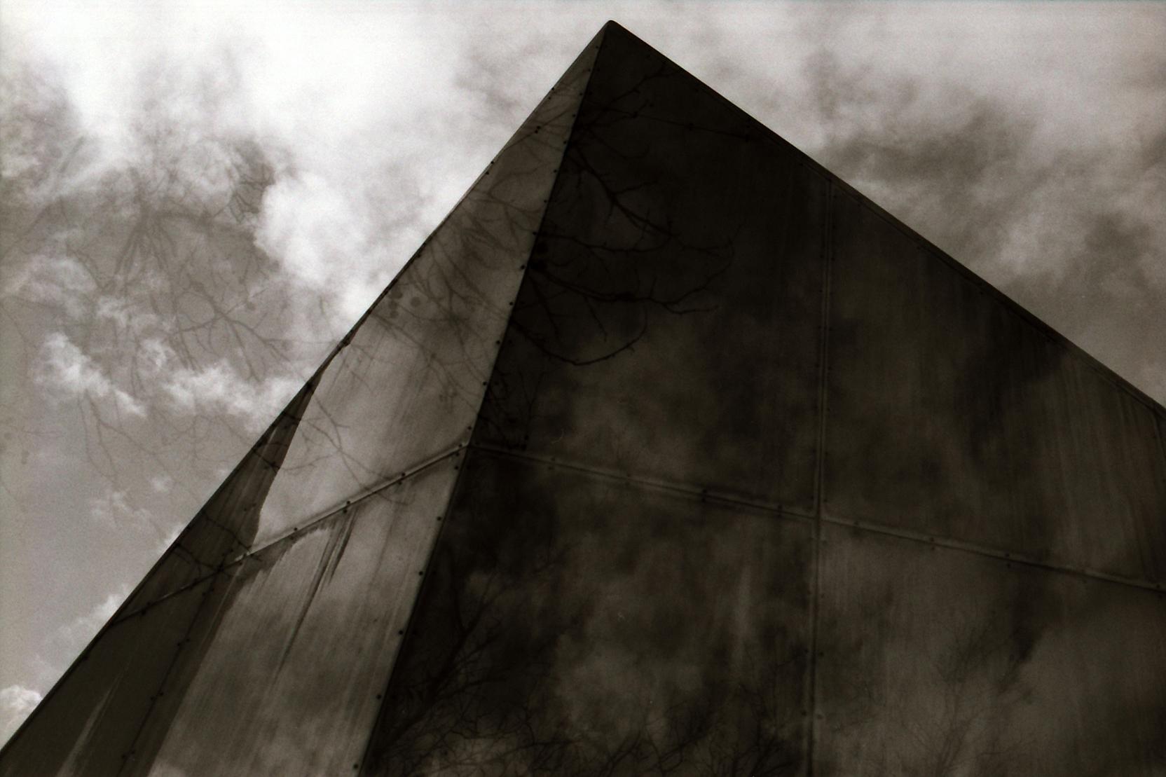 Doppelbelichtung mit Metallpyramide, Wolken und Baum