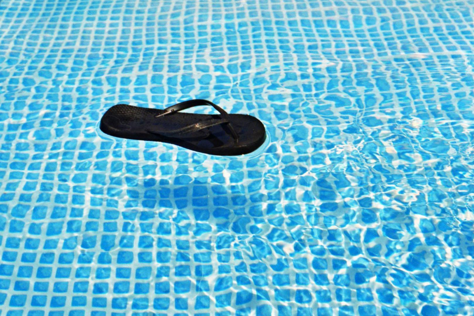 Schwarzer Flipflop in Swimmingpool