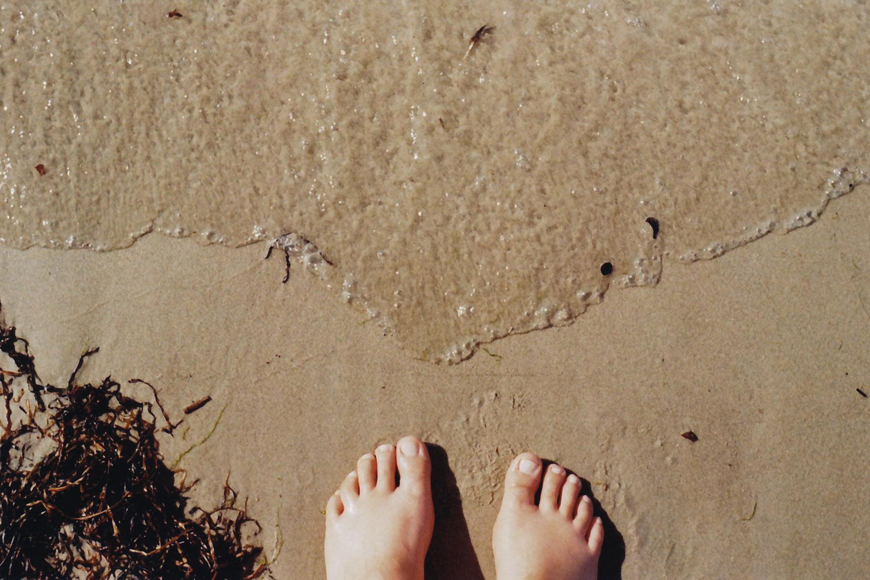 Nackte Füsse im Sand der Brandung