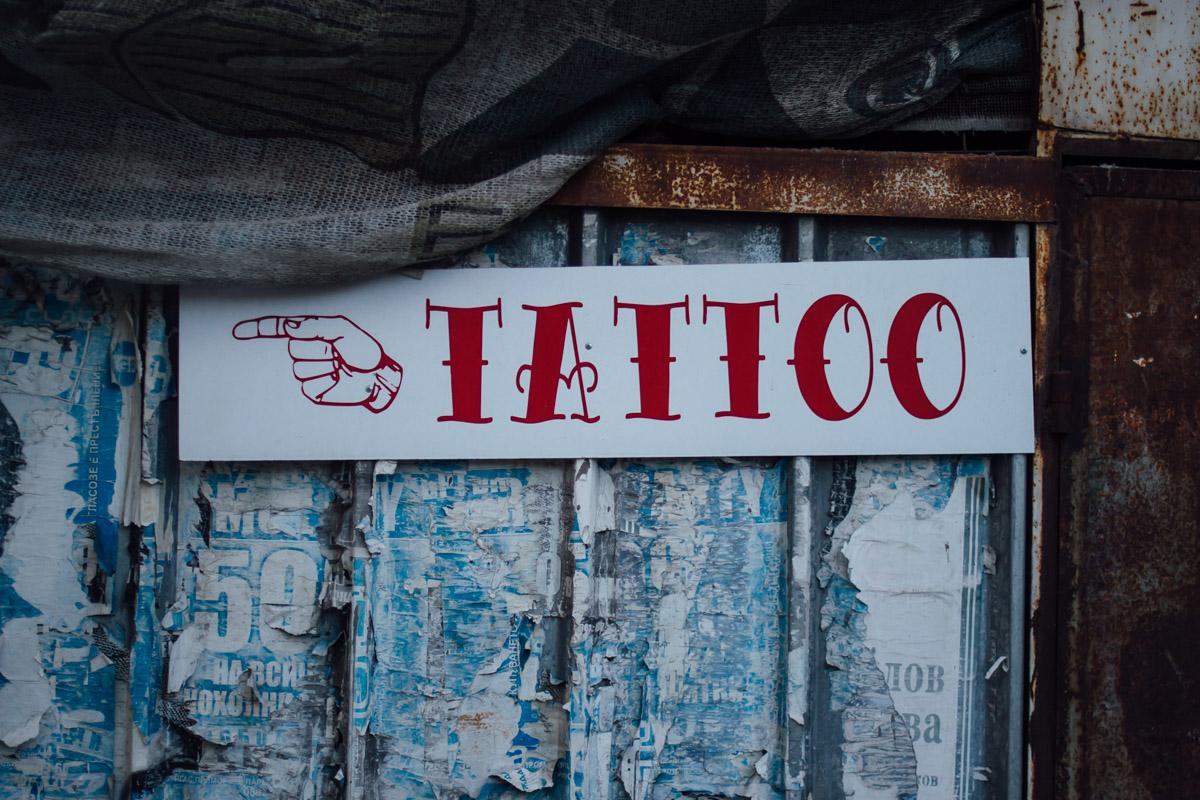 Tattoo-Schild an verwitterter Wand