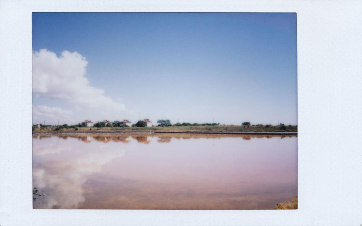Spiegelung von Häusern und Wolken im Salzbecken