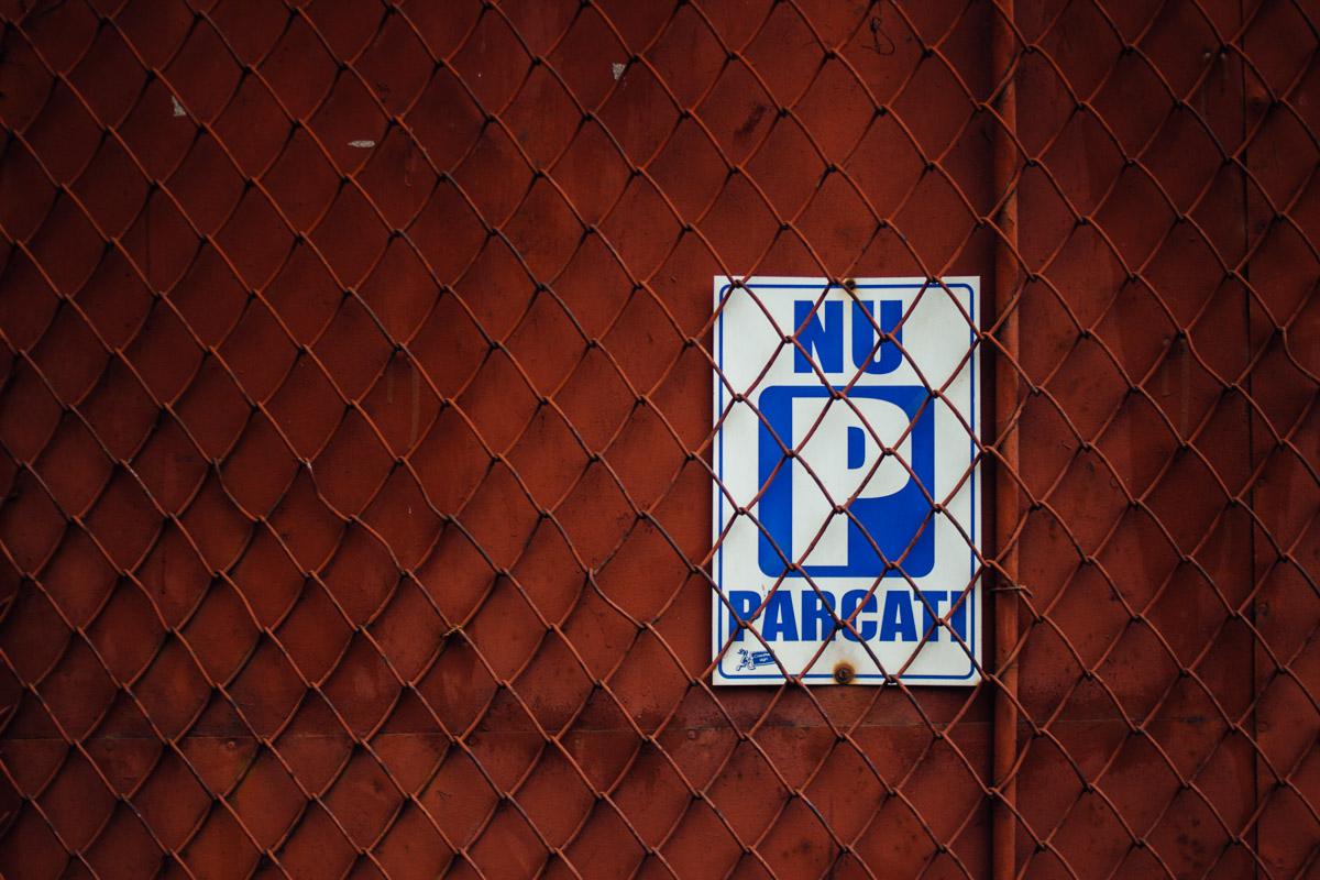Parkverbotsschild hiter Gitterzaun an orangeroter Metalltür