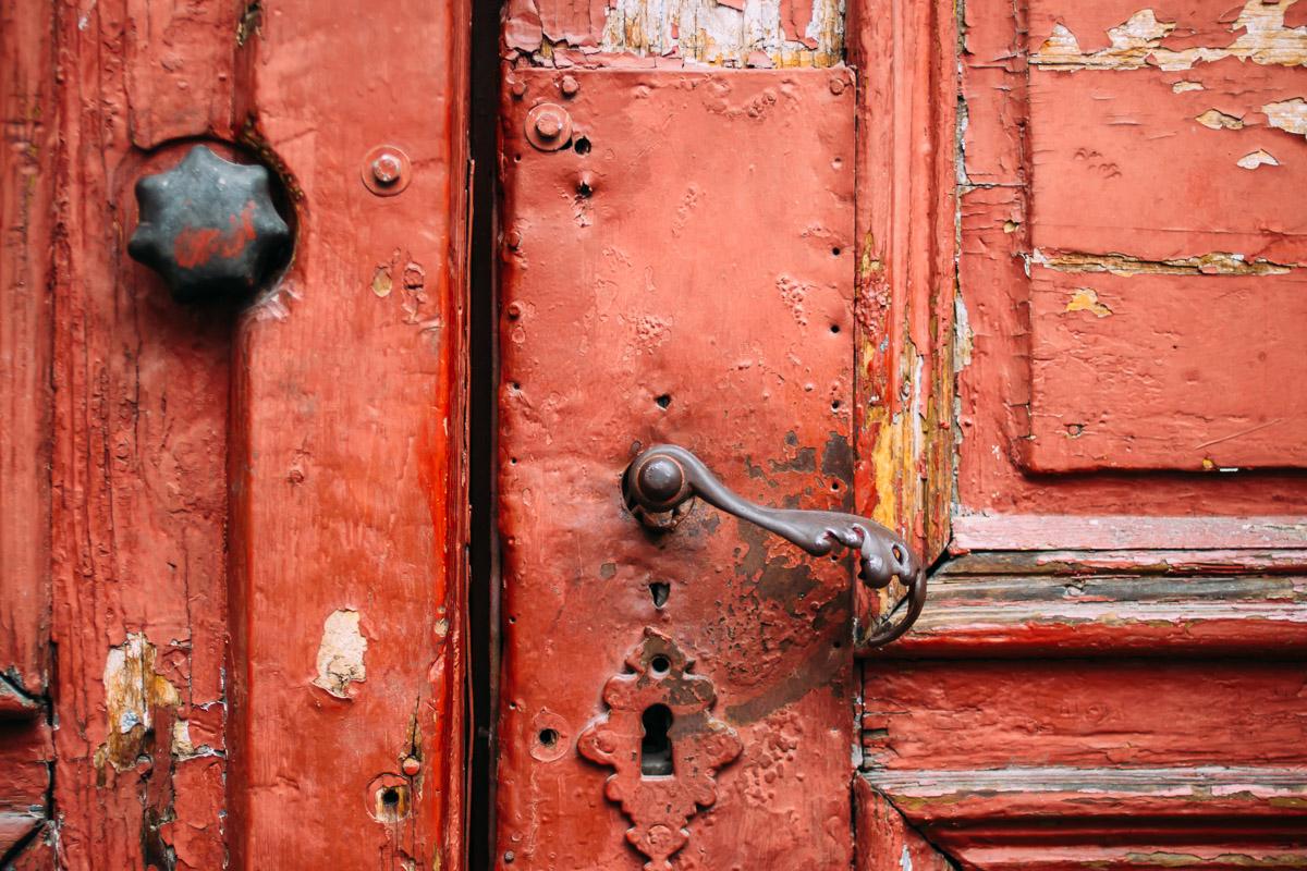 Alte rote Tür mit verzierter Türklinke