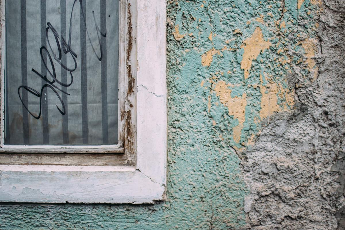 Ecke eines Fensters in Wand mit türkisfarbenen Putz