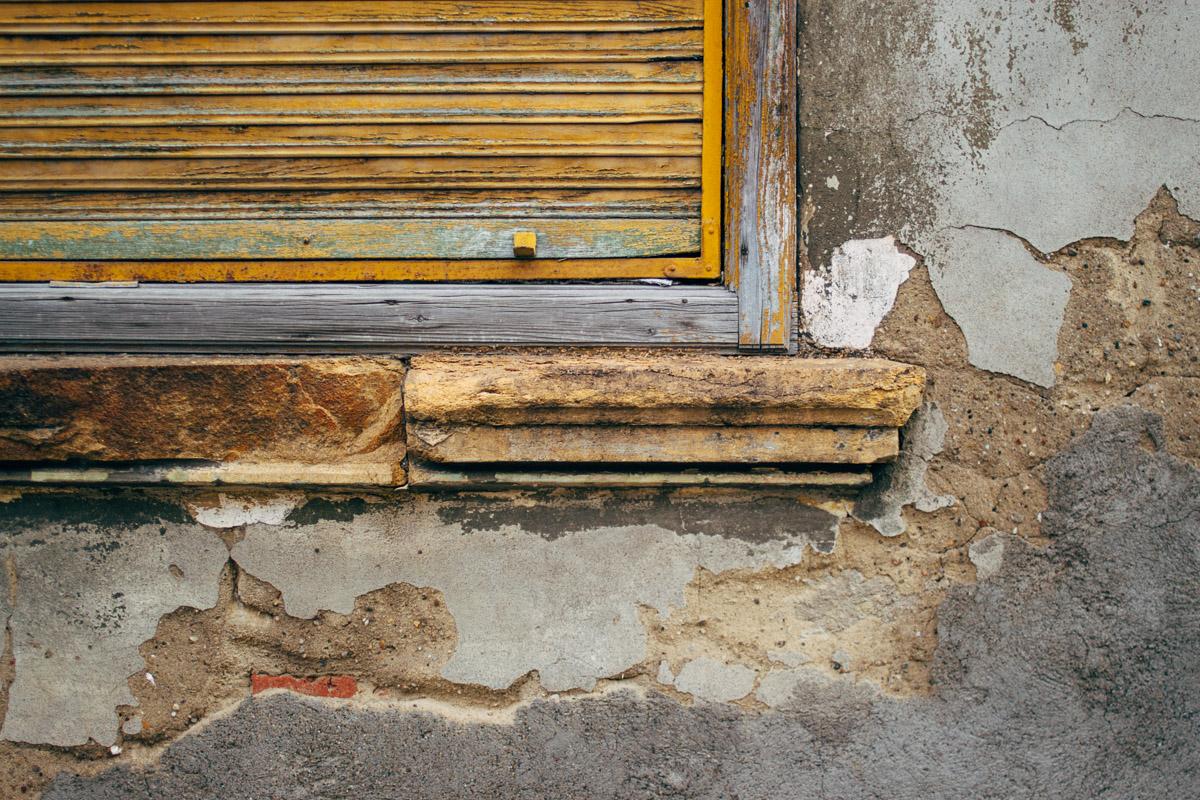Mit gelber Holzrollade verschlossenes Fenster