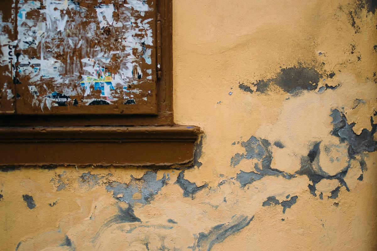 Ecke eines mit Metalltüren verschlossenen Fensters in gelber Wand