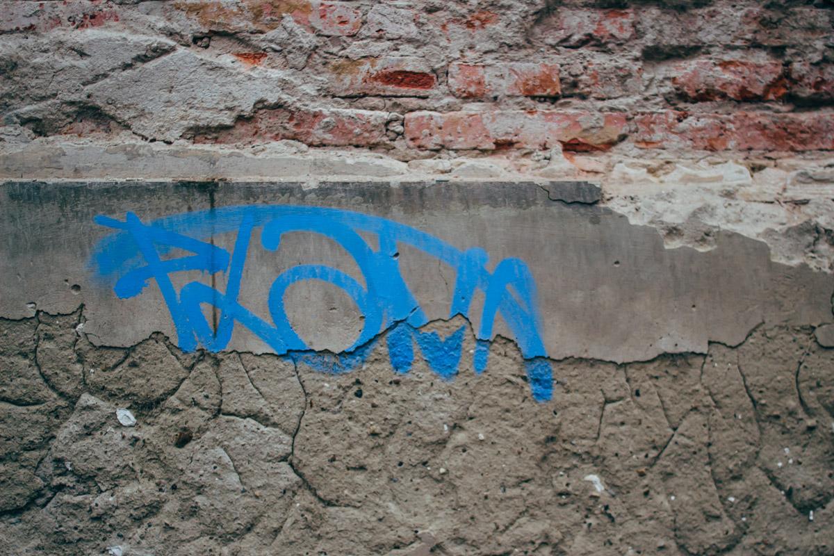 Blaue Schrift auf grauer Wand