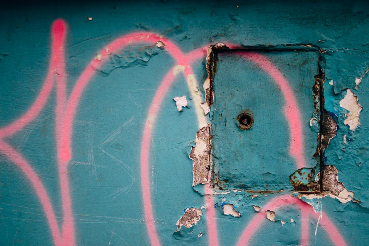 Pinke Schrift auf türkisfarbener Wand