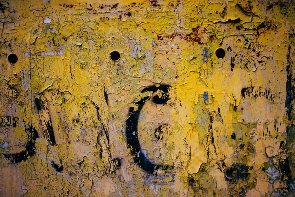 Reste von schwarzer Schrift unter gelber Farbe