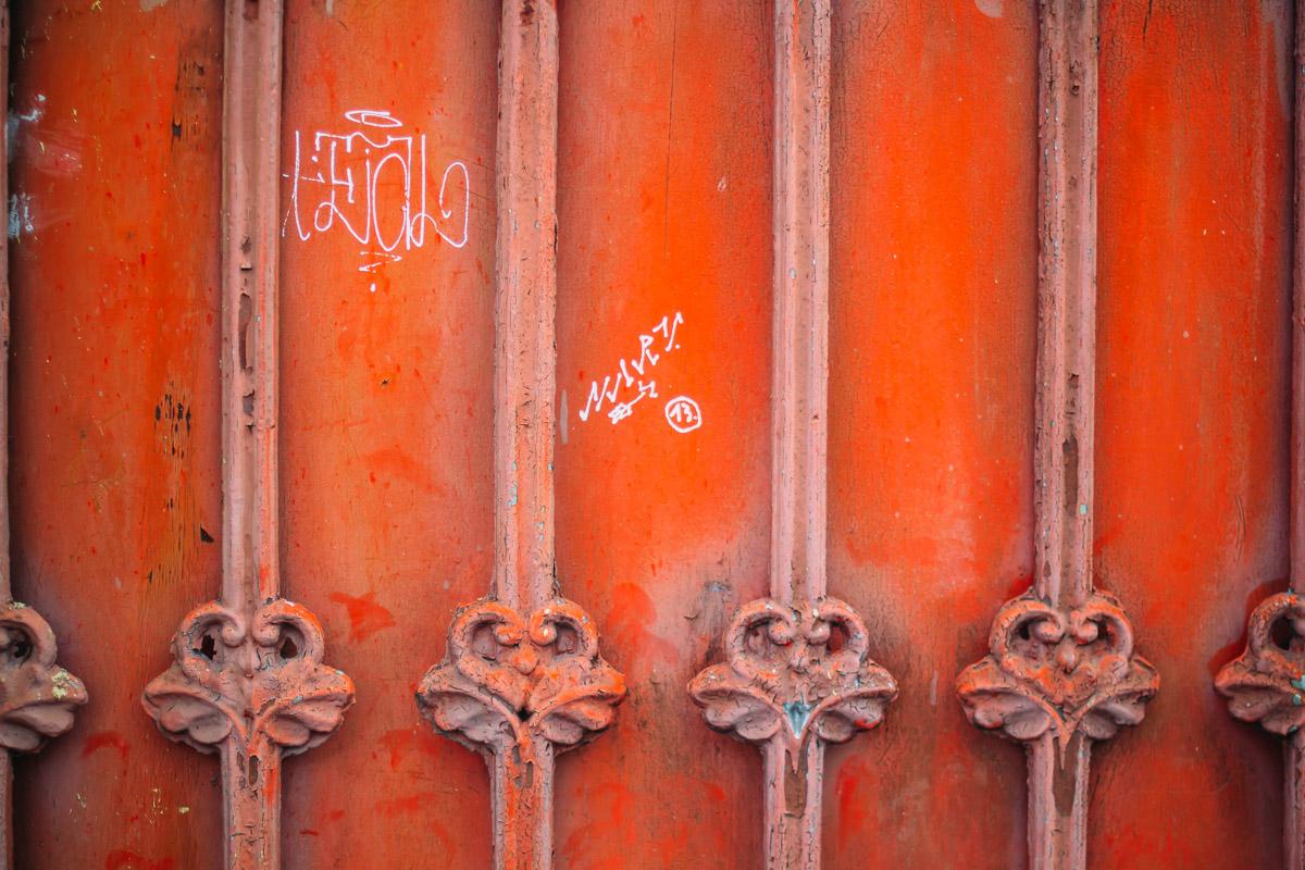 Weiße Kritzeleien auf orangen Zaun mit Metallornamenten